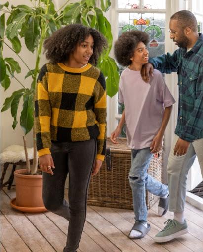Una giovane famiglia entra in una stanza dove ci sono una pianta e altre decorazioni sullo sfondo.