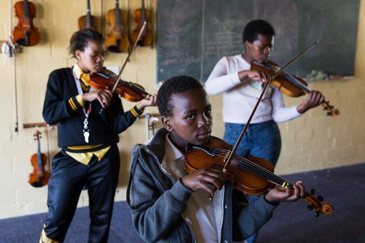Students learn to play the violin at the outreach programme in Masiphumelele, Cape Town.