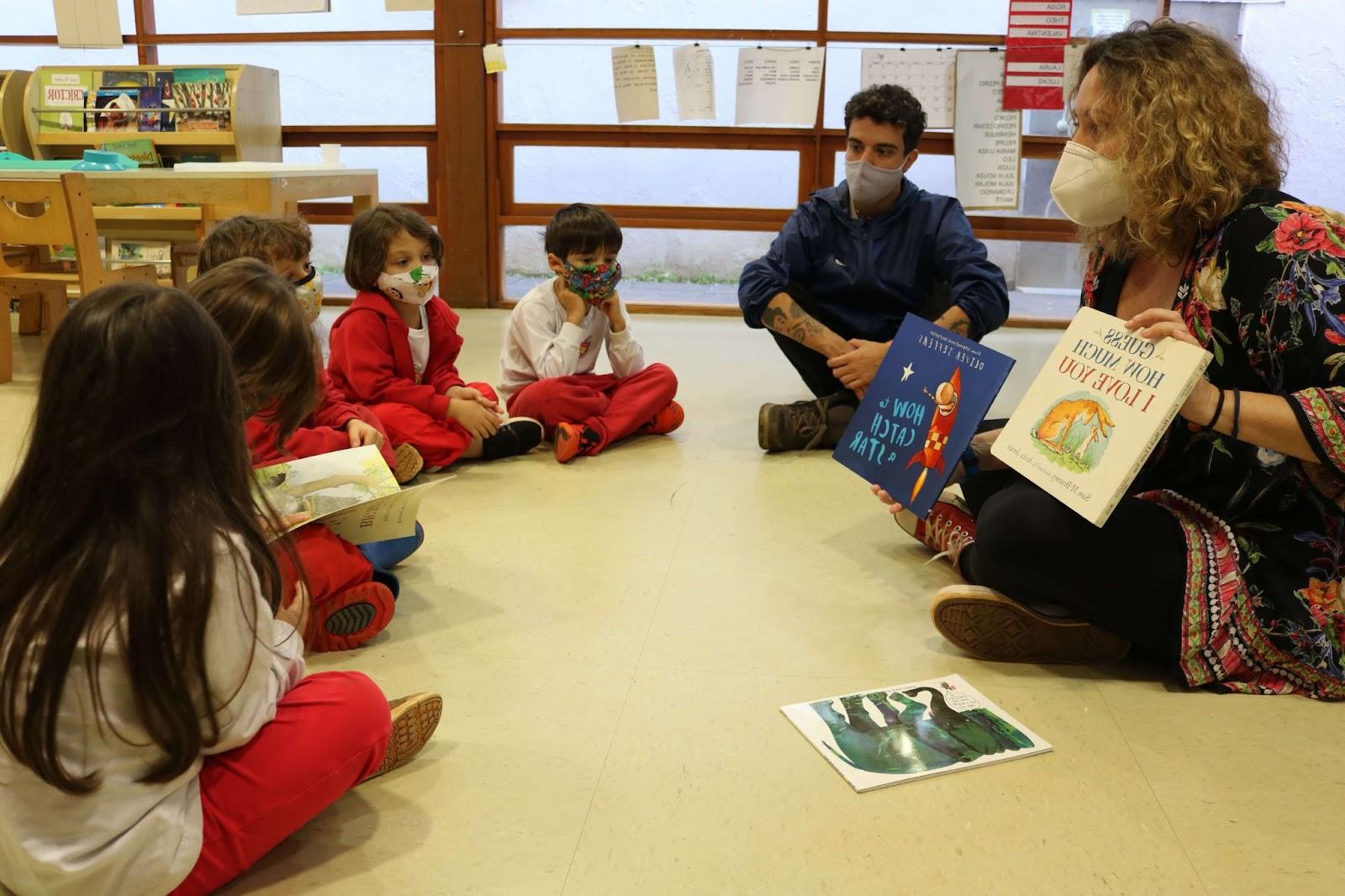 A imagem mostra um grupo de crianças do grupo Vermelho em uma roda de leitura de inglês em uma aula presencial.