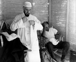 Photo: Alec Guinness retirando seu figurino enquanto David Lean descansa numa cadeira dentro de uma das diversas tendas montadas no meio do deserto para abrigar a equipe do filme.