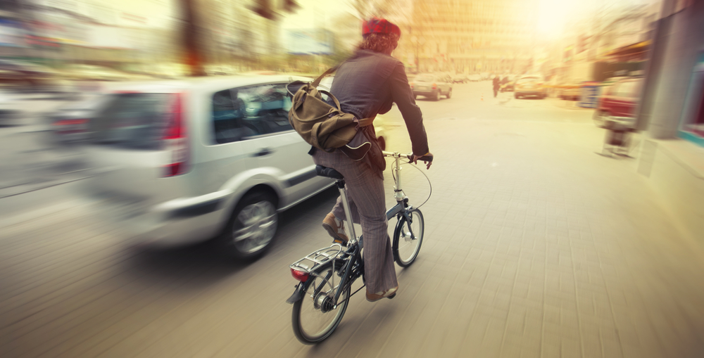 Homem andando de bicicleta com carro ao lado e blur na imagem
