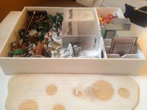 Photo: petite boite de rangement avec les dos des cartes d'ojets en fonction de leur couleur