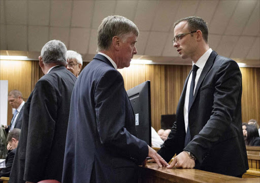 Oscar Pistorius (R) speaks to a member of his legal team during his trial at the high court in Pretoria, April 7, 2014.  REUTERS/Themba Hadebe/Pool