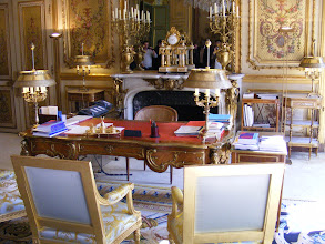 Photo: The office of the President of the Republic, the Salon Doré (Golden Room), retains the original 1861 decor by the painter Jean-Louis Gogon for Empress Eugénie. It is decorated with Gobelins tapestries, carpets from the Manufacture Nationale de la Savonnerie, a Napoleon III crystal chandelier and chest of drawers by Boulle. The masterpiece of this room (and said to be the most valuable item in the Palace) is the Louis XV desk by the 18th century cabinetmaker Charles Cressent, which was placed here at President de Gaulle's request. It took a few minutes to get this unobstructed picture, as most everyone lingered at this spot.