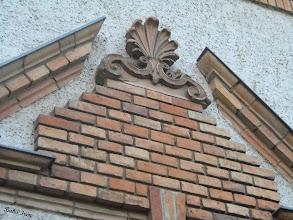 Photo: A bejáratok fölött stilizált nyitott timpanon