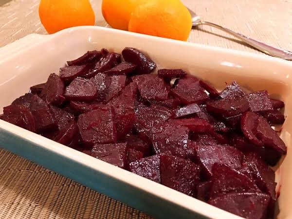Slices Of Beet In A Serving Dish With Oranges Behind.