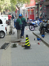Photo: Beijing - stinky Gulou West street with workers using sophisticated technology (manpower) to pull some wire through sewer system