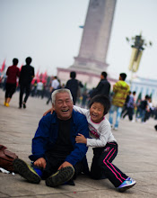 Photo: Boy and Grandfather at Tiananmen Square  I was walking through Tiananmen on a white-out cloud day taking photos of people. I had on my earphones and was kind of drifting in and among the crowd. It's a bit like being in a movie when you do this... anyway, I'm sure you've heard me mention it before, so I won't go into details.  It's often a very nice way to make things timeless... to separate people and objects from their place and time.  These two were on the ground wrestling and having fun.  I squatted about 15 feet away to take a photo, and they were most delighted!  From the blog at stuckincustoms.com