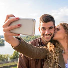 Happy young couple taking selfie photos near the river by Vera Arsic - People Couples ( young women, romance, two people, heterosexual couple, friendship, city life, togetherness, young adult, river bank, kissing, selfie, connection, model, communication, smiling, attractive, smart phone, telephone, lovers, lifestyles, girlfriend, enjoyment, color image, adult, photography, city, boyfriend, affectionate, modern, romantic, happiness, joy, dating, flirting, caucasian ethnicity, nature, carefree, sexy, intimate, young men, technology, people, love emotion, young couple, outdoors, bonding, couple relationship, fun, laughing )
