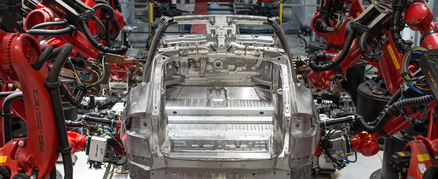 Tesla's automated assembly line with robots assembling the frame of a car.