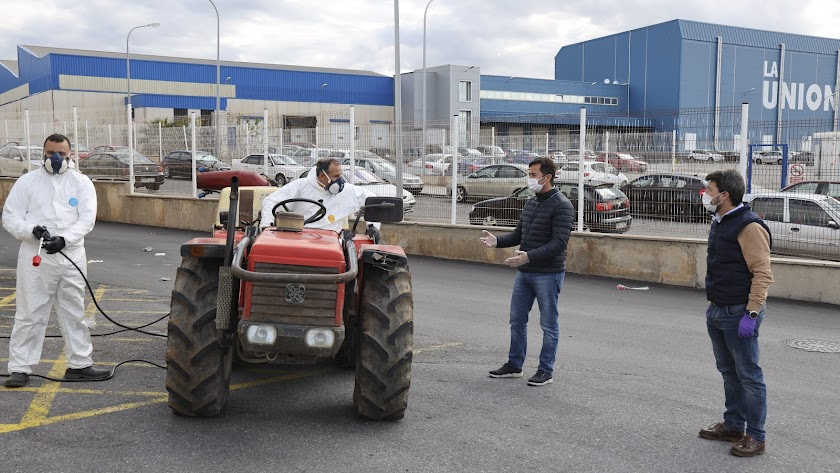 Agricultores con su tractor y traje protector junto al alcalde de El Ejido.
