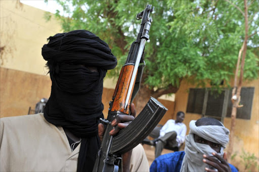 A picture taken on July 16, 2012 shows fighters of the Islamist group Movement for Oneness and Jihad in West Africa (MUJAO) sitting in the courtyard of the Islamist police station in Gao. A West African military force assembled to intervene against Islamic radicals in Mali is ready to be deployed.