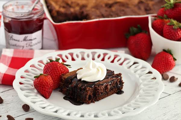 A Slice Of Double Chocolate Strawberry Gooey Butter Cake With Chocolate Drizzle.