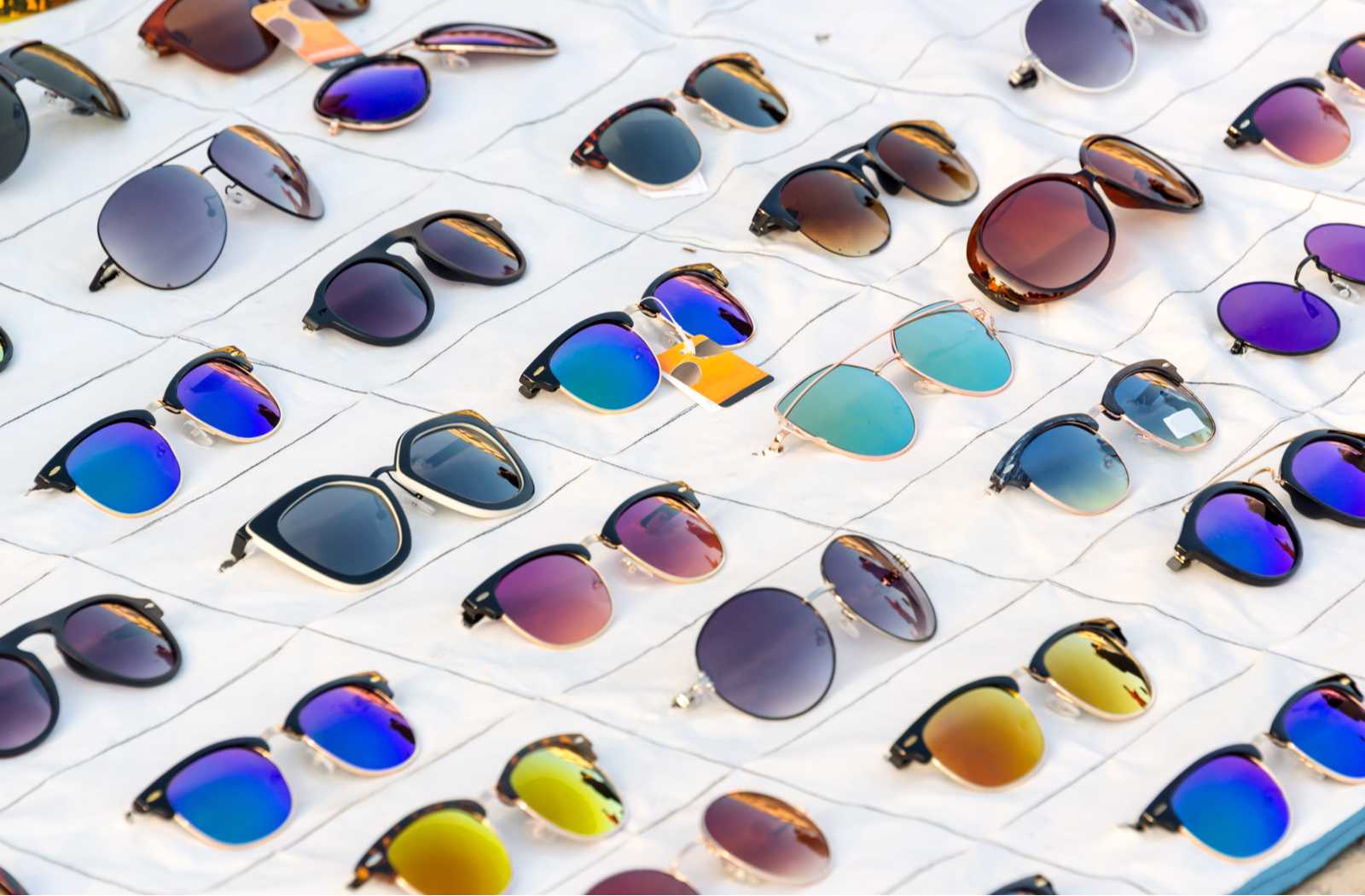 Colourful lenses and fashionable glasses arranged on a display canvas