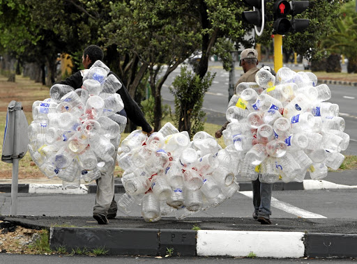 Two men in Cape Town carry plastic bottles for recycling. PET, or polyethylene terephthalate, used to make water bottles, is the fourth-most produced plastic in the world. Picture: ESA ALEXANDER