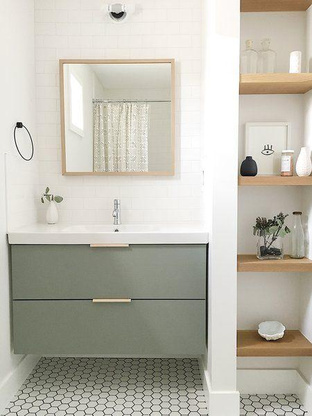 Banheiro com azulejo subway tiles branco na parede da pia, armário verde com bancada branca, piso hexagonal em formato pequeno combinando com armário e prateleiras de madeira com objetos decorativos.