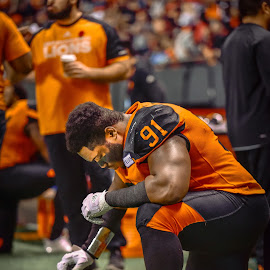 Taking A Knee by Garry Dosa - Sports & Fitness American and Canadian football ( sports, teams, players, black, cfl, football, lighting, people, orange, indoors, stadium, praying, kneeling )