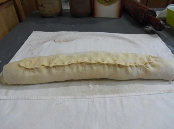 Crimp the dry end to roll of dough to secure. Turn the roll with...