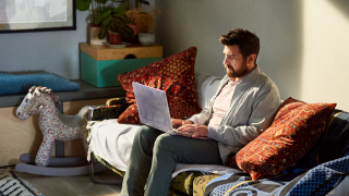 image of man sitting on couch with laptop