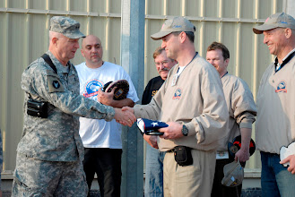 Photo: Commanding general of Multi-National Division South, Maj. Gen. Rick Nash, presents the 3000th flag to fly over COB Basra to a member of Serving our Troops Dec. 18. This event also kicked-off the 373rd birthday of the National Guard.