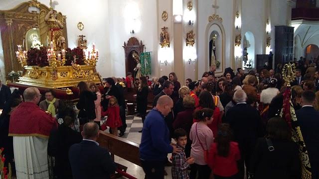 El pasado año, tras la suspensión de la procesión por la lluvia, el párroco dando a besar la Santa Cruz del Voto.