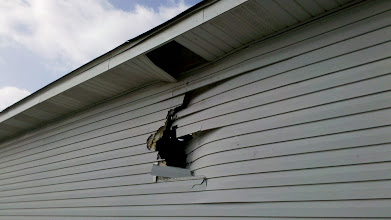 Photo: Neighbor's house.  The 120mph winds picked up some plywood he had stacked in his yard and it ripped a hole in his house.