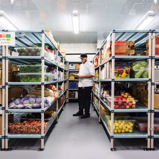 Young man standing between two shelves of various produce, looking down at his clipboard