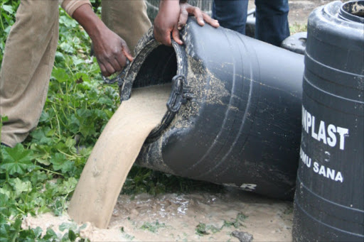 Police pour chang'aa during a crackdown on illicit liquor.