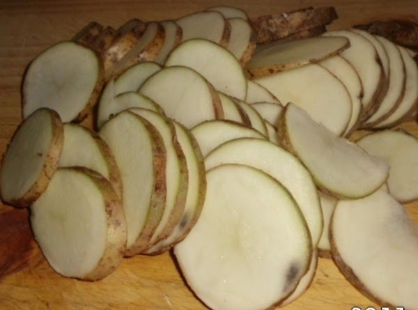 Wash potatoes, you can leave skin on, or peel.  Slice potatoes into THIN...