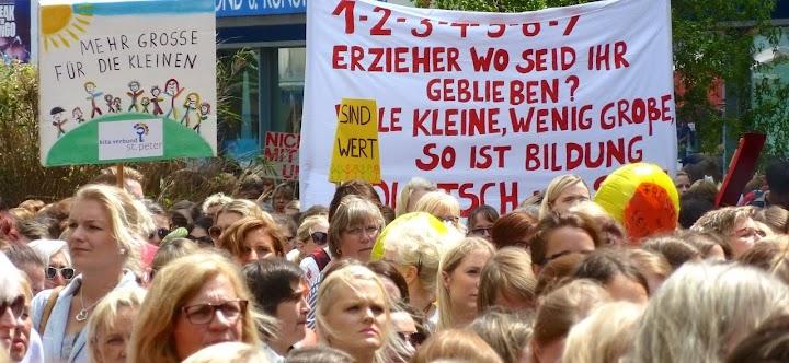 Demonstrantinnen mit Transparenten: «Mehr Große für die Kleinen», «1, 2, 3, 4, 5, 6, 7 – Erzieher wo seid ihr geblieben? Viele Kleine, wenig Große, so ist Bildung Quatsch mit Soße».