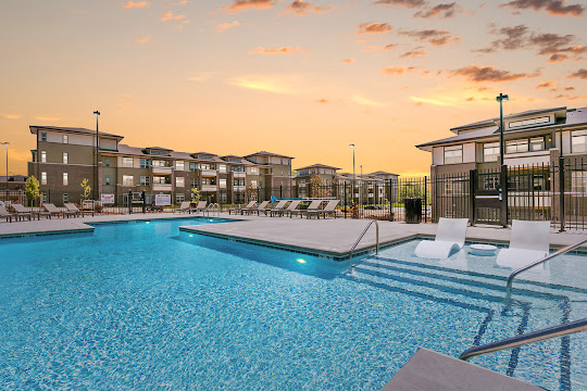 Brookside's swimming pool at dusk with white lounge chairs in shallow end and lounge chairs surrounding pool