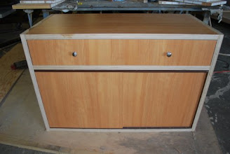 Photo: 2 toned kitchen cabinet featuring a large central drawer and 2 sliding doors for the bottom of the cabinet, with room enough to store almost an entire kitchen in it