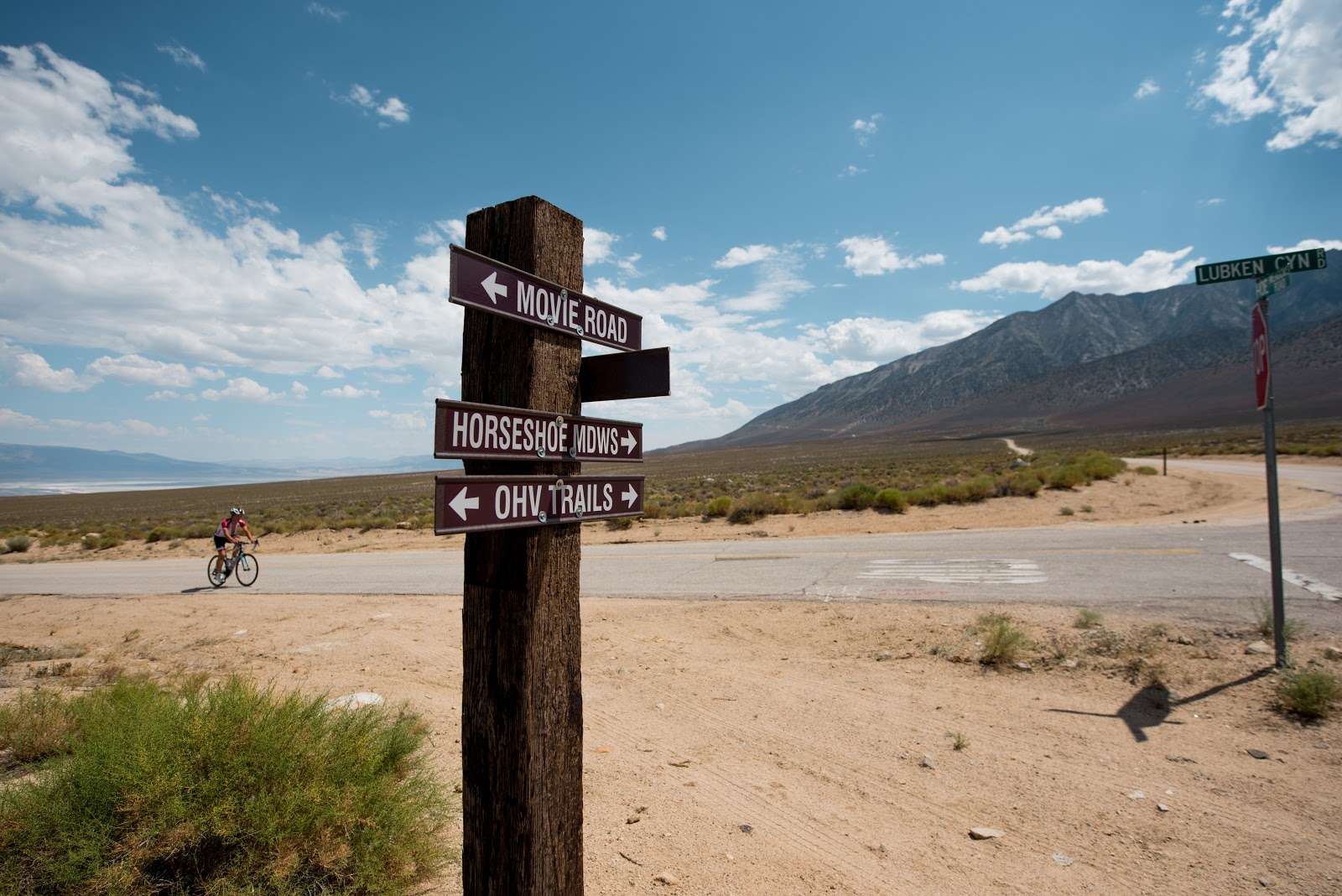 Cyclist riding bike at intersection of Lubken Canyon Road and Horseshoe Meadow Road Big Pine, Owens Valley
