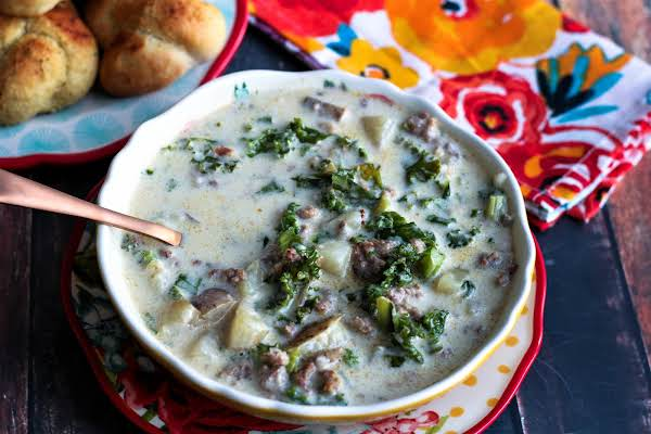 A Bowl Of Zuppa Toscana With A Spoon.
