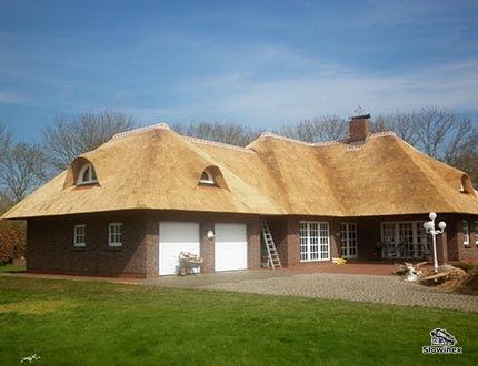 Niski dom z garażem i dużymi oknami połączony nowym dachem trzcinowym