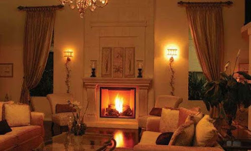 a fireplace in a lounge with a warm fire burning