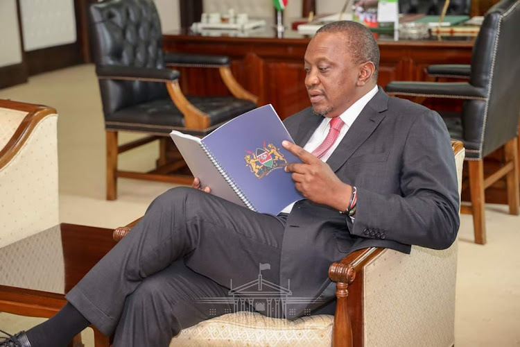President Uhuru Kenyatta reads the BBI report.