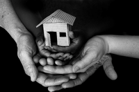 multiple hands holding a miniature house symbolizing unity