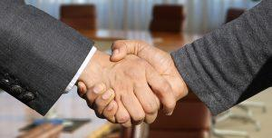 Two people in business attire shaking hands.