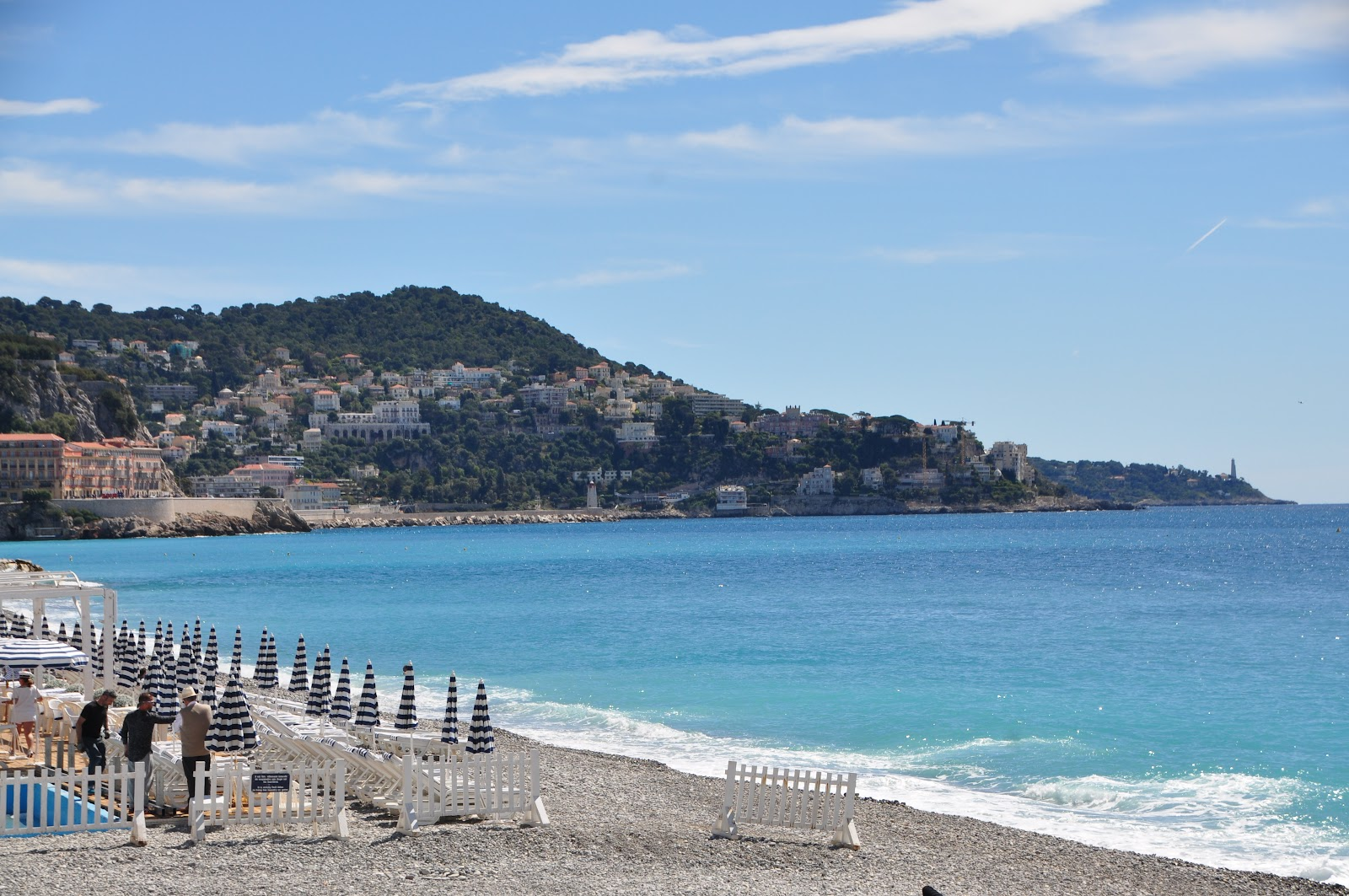 Plage Blue Beach nice france pebble beach during off-season, no tourists, pretty blue sea and calm waves, green hill and villas in the background on a sunny day in cote d'azur, french riviera.