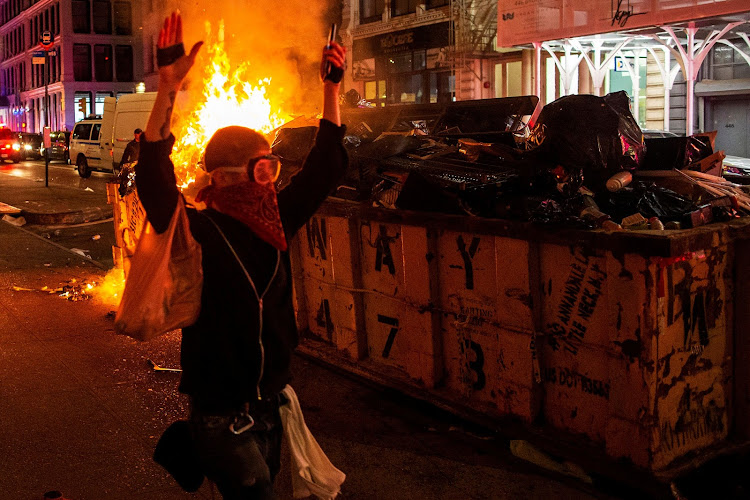 A protester walks with his hands up while looting after marching against the death in Minneapolis police custody of George Floyd, in the Manhattan borough of New York City on Monday.