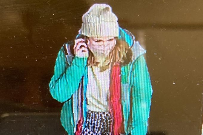 A screenshot of a woman in a beanie, face mask and green coat walking while speaking on the phone