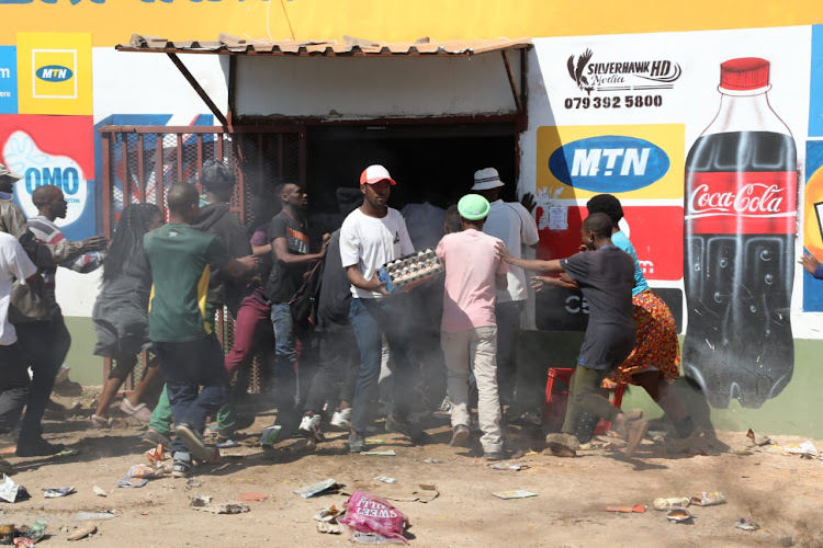Residents of Jabavu in Soweto loot a foreign-owned tuck shop on August 29 2018.