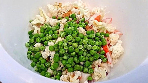 In a medium bowl, add chopped crab, onion, celery, seasonings, peas, cauliflower and cheese....