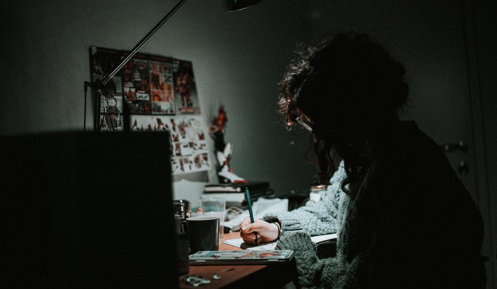 Man drawing at desk late at night