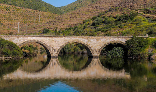 Portugal-Douro-bridge - A Douro River bridge near terraced hillsides in Portugal.