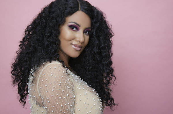 A Latina woman wearing makeup standing in front of a pink background