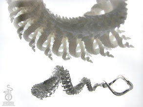 Photo: Spiralling spirals sterling silver 3D fractal pictured with a larger sculpture version in SLS nylon