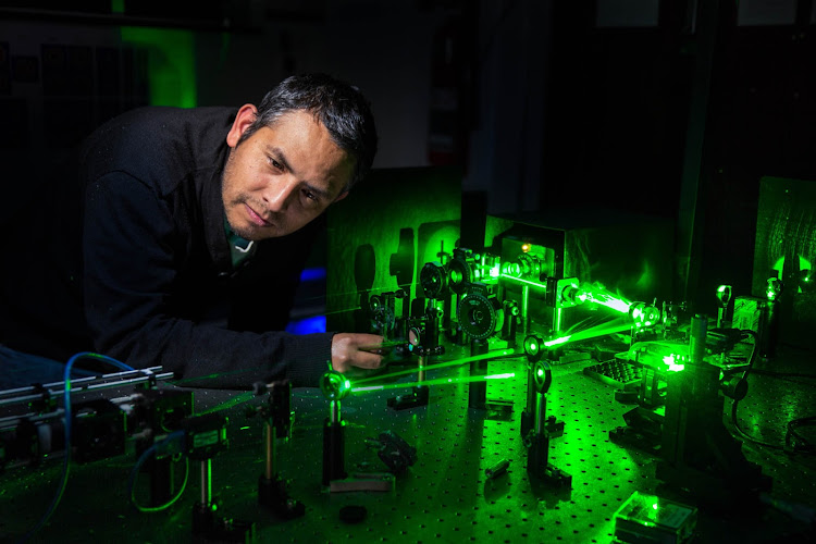 Carmelo Rosales works with a laser in the Structured Light Laboratory at the University of the Witwatersrand in Johannesburg. Rosales, a post doctoral researcher, is working with Andrew Forbes and his team on data communication via laser light. Rosales says that the team can produce light one photon thick that is encrypted and virtually hack-free. The applications for this technology can help poor communities receive cheaper broadband access; can be used in military applications and banks have shown interest in the technology for communicating between branches.