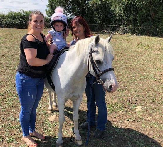 Baby on a pony with mother and horse-trainer